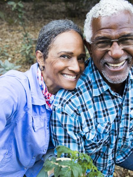 An attractive senior black couple working in the garden taking a selfie with their smartphone